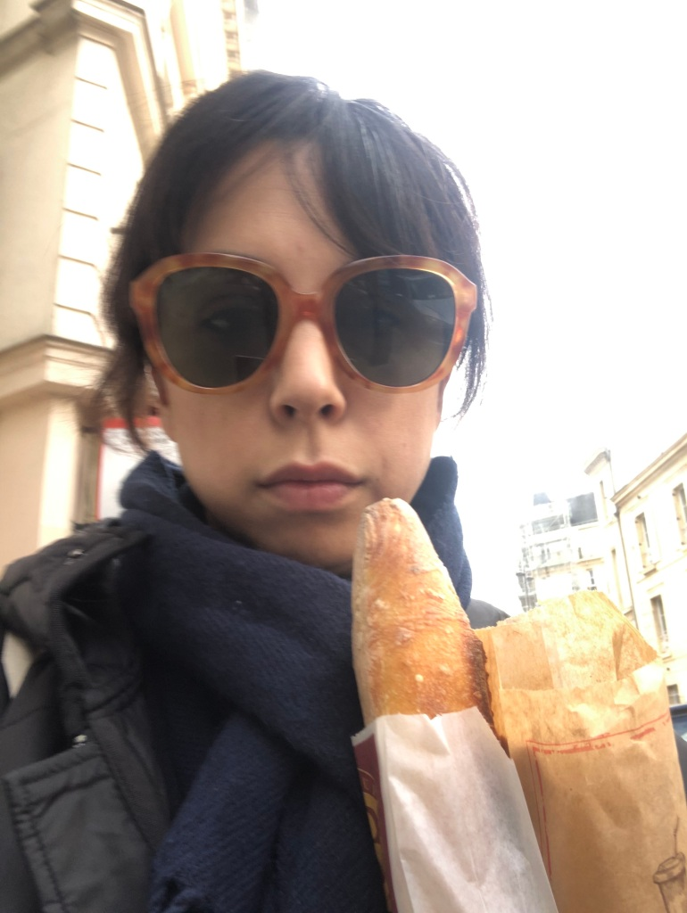 Shelby wearing sunglasses and holding baguettes